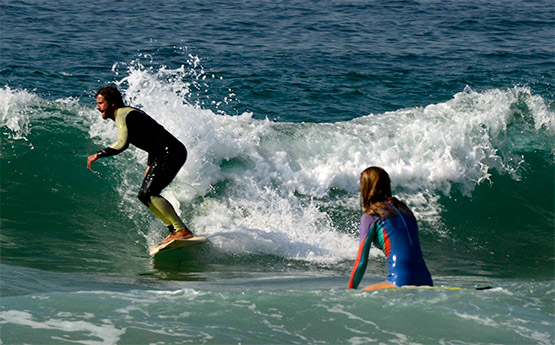 A surfer manages to stay upright at Manly Beach, Sydney