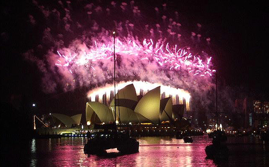 A cloud of pink created by the Sydney Hrbour New Year's Evev fireworks illuminates the Sydney Opera House in 2005